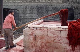 Il filato viene immerso ripetutamente nelle grandi vasche di colore per essere tinto in maniera uniforme.